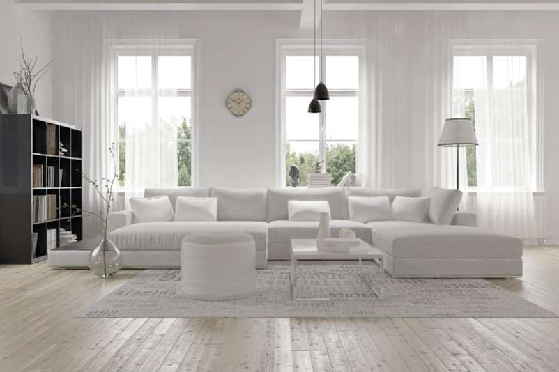 a white living room with three big casement windows and white furniture.
