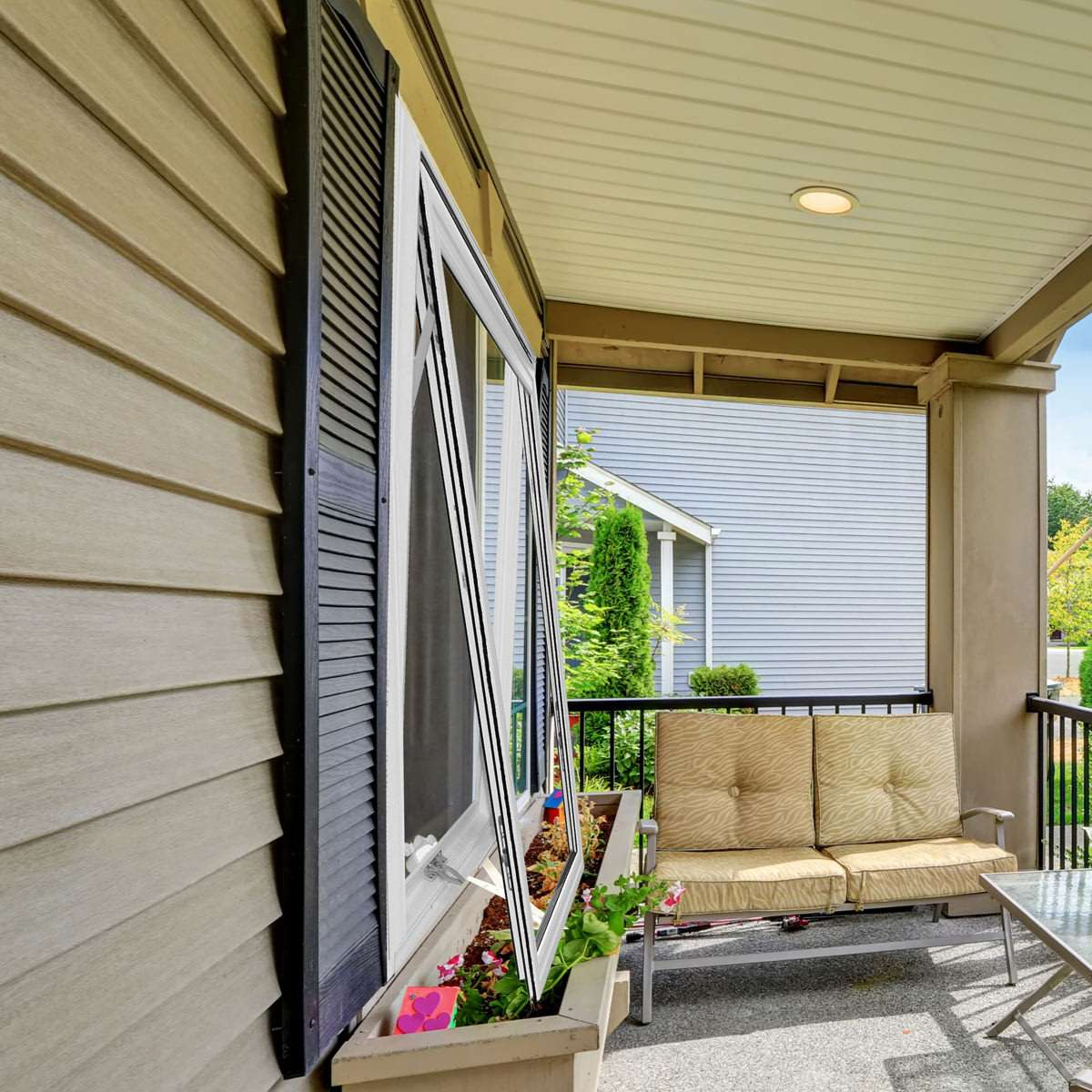 Side of a house with an open white awning window and an outside furniture set on the deck.