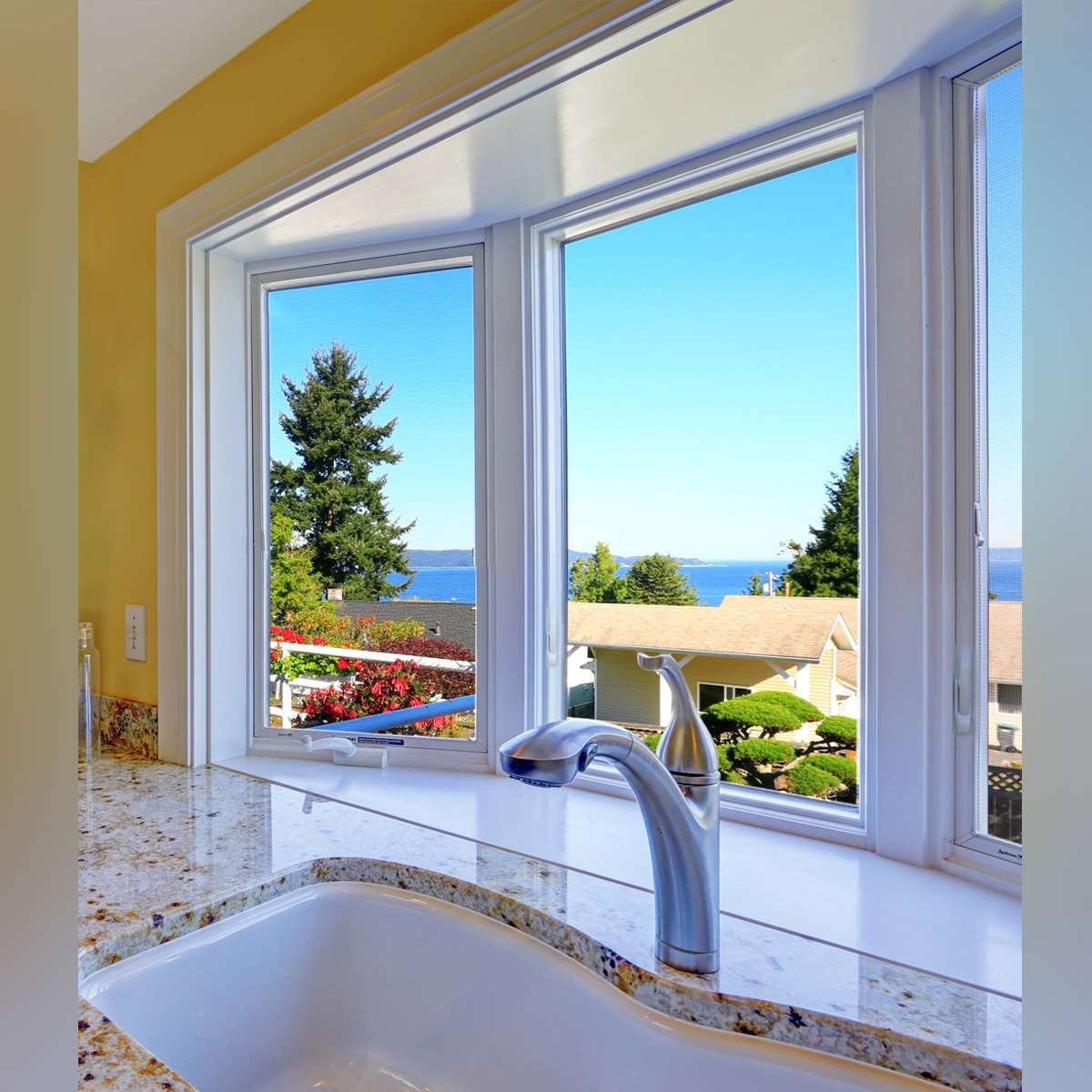 White sliding window on a yellow kitchen wall, with a backyard view and clear skies.