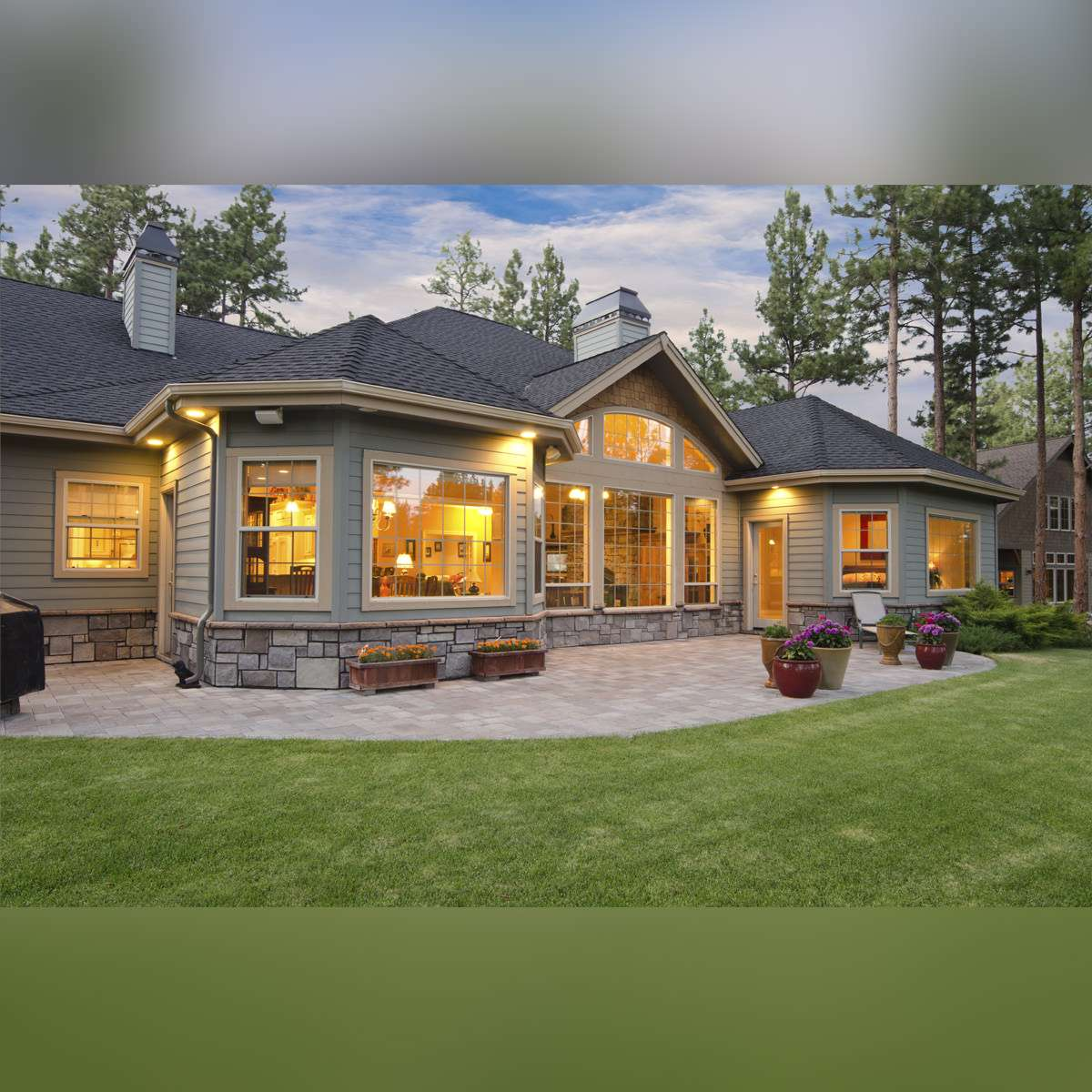 Backyard big house with grey roof and Alumhybrid architectural windows.