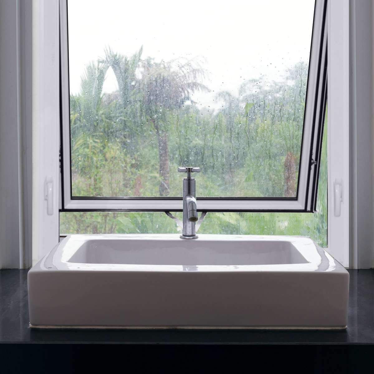 Awning window above a white sink with rainy view with green trees