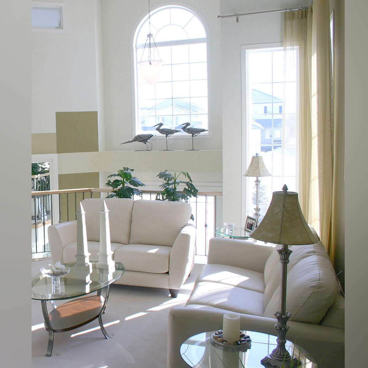 White architectural windows in a white and bright living room with white couches and a golden lamp.