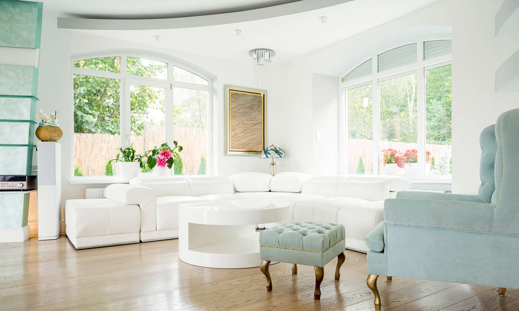White architectural windows in a white and green, bright living room.