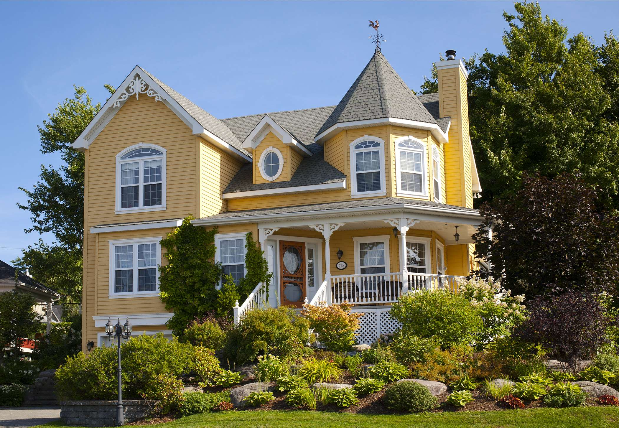 Yellow house with white windows and a garden