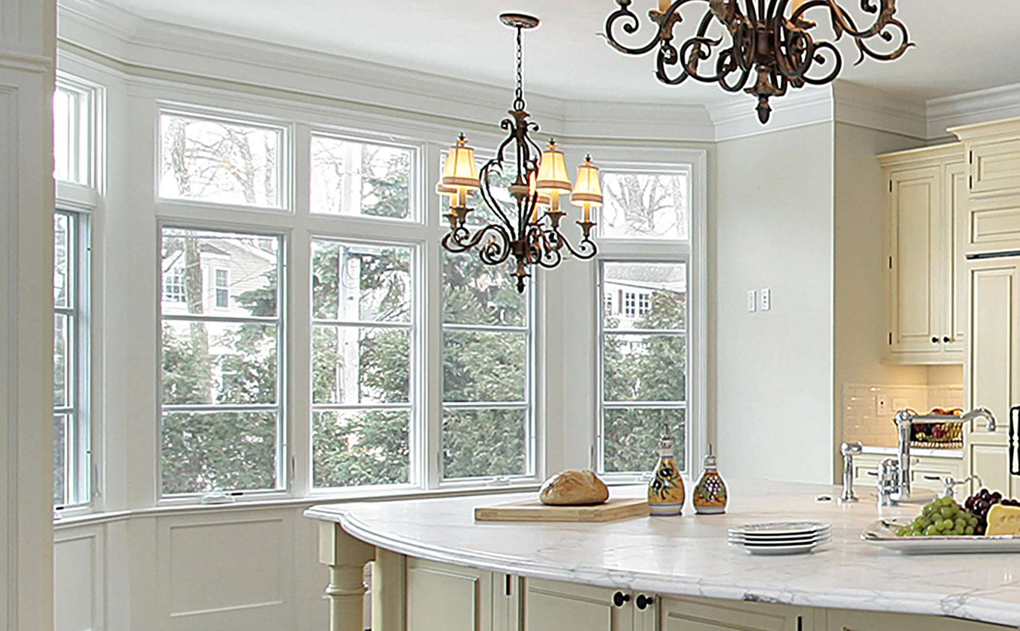 White kitchen with chandelier and bay/bow window