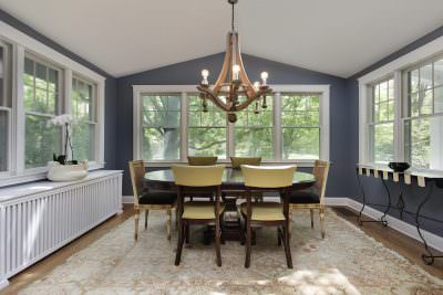 White hung windows in a blue dining room with a yellow table set and a bright chandelier.