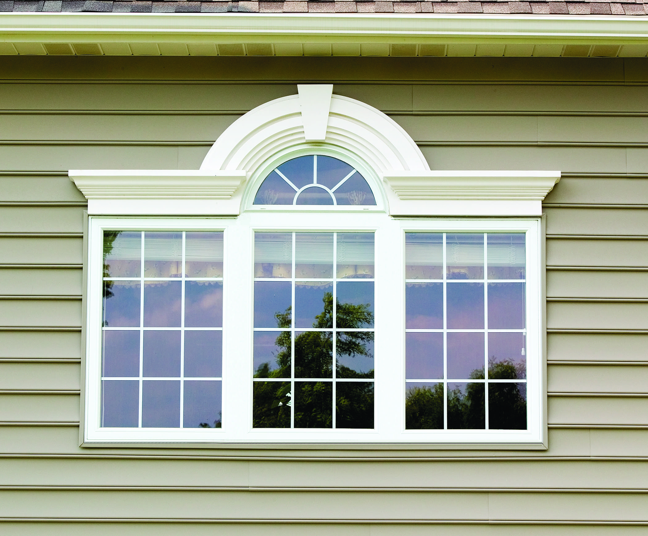 Khaki siding with a white window