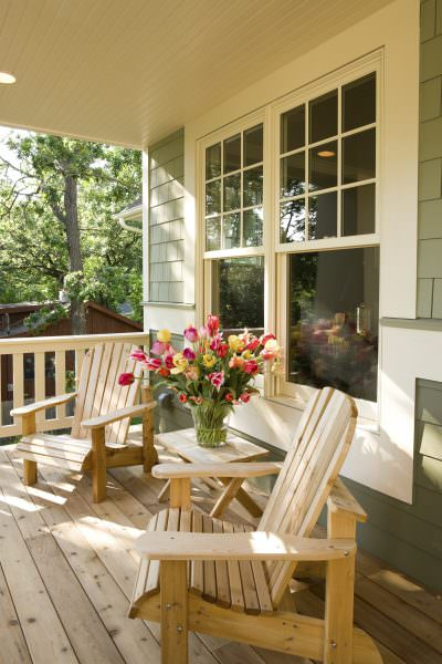 Beige porch with two chairs, a table, a vase full of flowers and two hung windows.