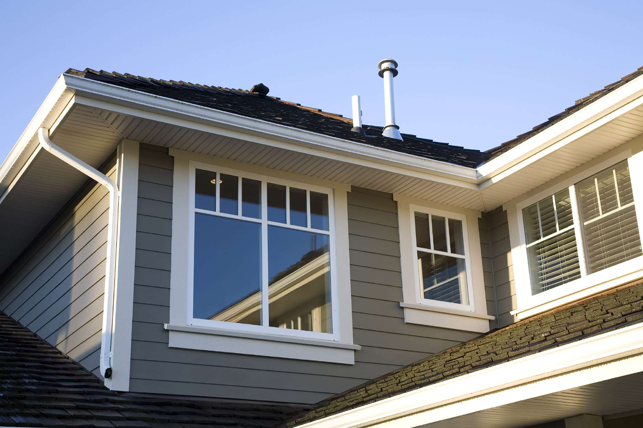 Gray siding with a black roof and a few white hung windowsé