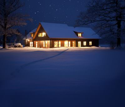 A lighted house in the middle of a winter setting.
