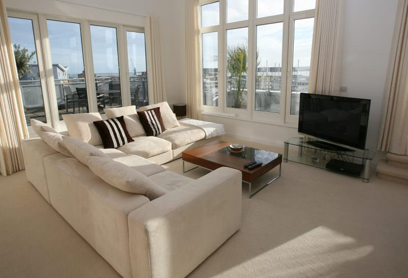 White living room with a white couch, a plasma tv and bow windows.