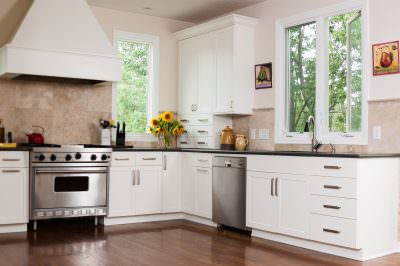 White kitchen with casement windows, providing a a green view