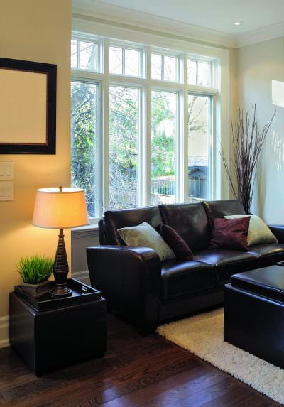 living room with dark leather couches and a big white bow window