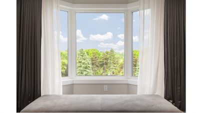 White bow/bay window with light and dark curtains, with a view of a clear blue sky and trees.