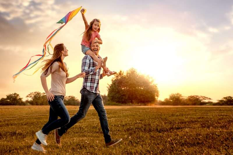 Aamily running through a sunny and green field, flying a kite.