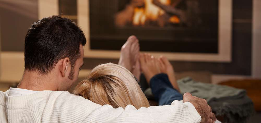 Couple relaxing in front of the fire place with a gray blanket.