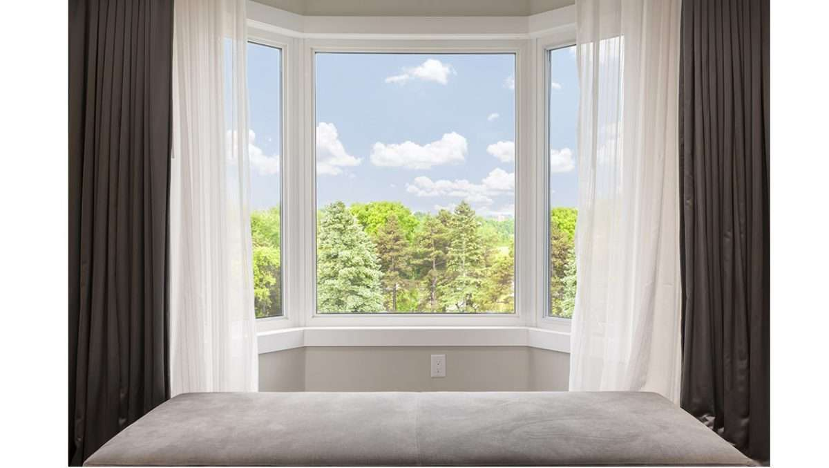 A bow window with white and dark curtains with beautiful view.