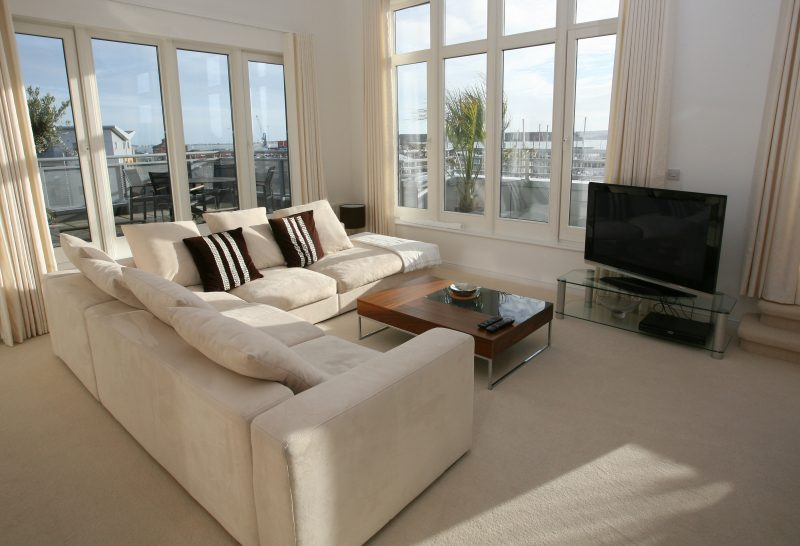 White living room with white suede couches, a brown coffee table and wide bay windows.
